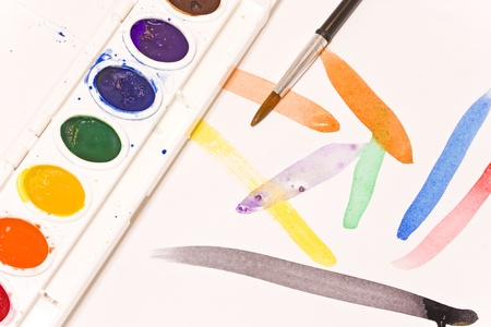 Simple brush strokes   Wet watercolor paintbrush strokes on bright white paper  Watercolor set with multicolor palette rests on the paper  Paint droplets cover the white plastic paint container Stock Photo - 16848870