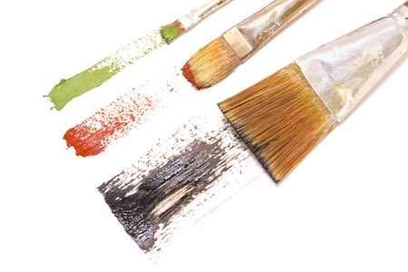 3 brushstrokes   Three artists brushes, thin, medium, and wide bristles paint wide green, red, and black brush strokes across bright white paper  Horizontal view  photo