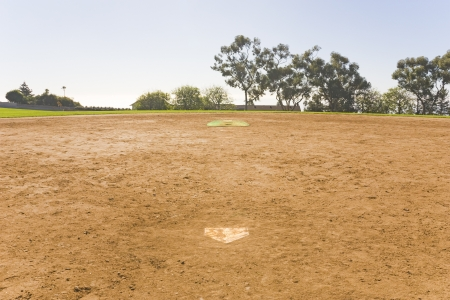pitchers mound: Vacant playing field   Horizontal view of a vacant baseball field in a suburban park in the daytime  Perspective is on the infield, behind home base  Dirty home plate  Trees and blue sky in the background  Stock Photo
