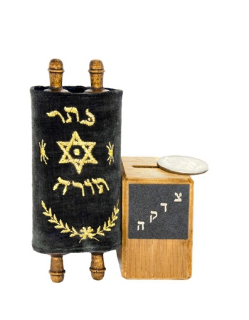 Mini Torah and tzedaka box with coin   Photo shows a small Torah next to a wooden charity box with a silver dollar on top of the box  The cover of the Torah scroll is soft, blue cloth with the Hebrew words  photo