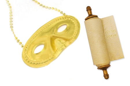 esther: Purim mask and Scroll of Esther   Shiny, gold color mask and Megillah scroll for the Jewish holiday of Purim  Celebration of the holiday includes wearing costumes, masks and reading the Megillah  The scroll is rolled up on a wooden roller  Stock Photo