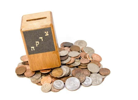 Wood tzedakah box on an assortment of coins   A small wooden tzedakah box, or charity box, on top of a pile of coins  The word tzedakah is written in Hebrew letters on the box  Horizontal view, isolated on a white background  photo