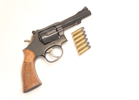 six shooter: Classic six shooter with bullets  Profile of a  38 caliber handgun with wood grip  Six shiny bullets just below the gun  Isolated on a white background