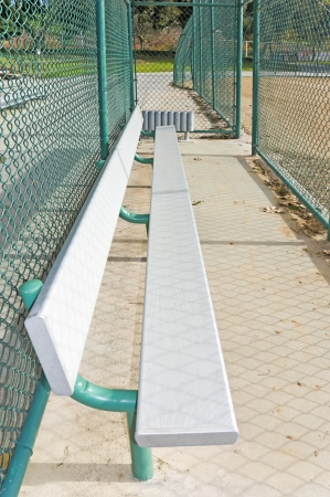 baseball dugout: Baseball dugout    Perspective, angled view of a bench in the dugout behind a chain link fence in a suburban park   Stock Photo