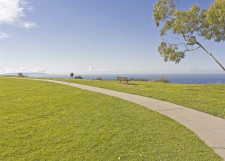 overlooking: Cliff top perspectiva esc�nica vista gran angular de una trayectoria curva pavimentado en un parque suburbano bancos de madera se siente en la cima del acantilado domina el cielo azul, las nubes y los oc�anos