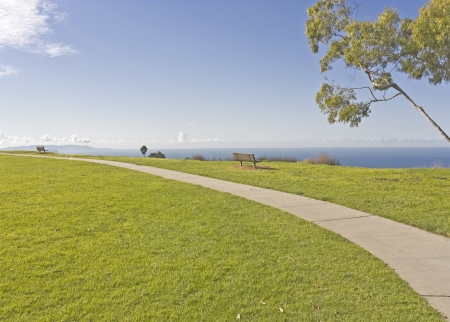 Cliff top scenic view    Wide angle perspective of a curving paved path in a suburban park  Wood benches sit on the cliff top overlooking the blue sky, clouds, and ocean  photo