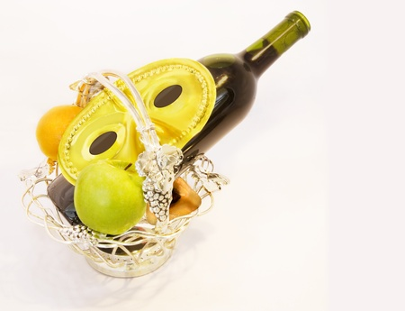 Purim basket    A custom for the Jewish holiday of Purim is to send gift baskets of food and drink to friends  This is called Mishloach Manot, or Shalach Manot  Shown is a decorative silver basket with fresh fruit, wine bottle, and Purim mask  Stock Photo - 17153865