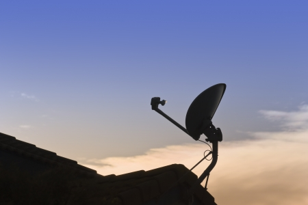 parabolic mirror: Home satellite dish at sunset    Silhouette of a roof mount residential dish antenna at sunset  Stock Photo