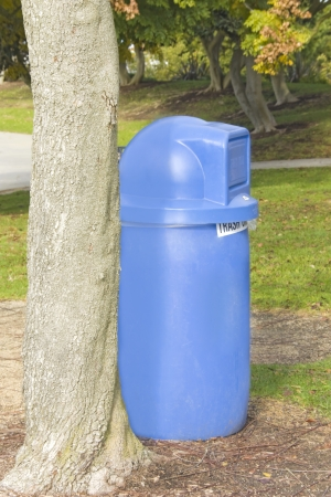 Keep our park clean    A blue plastic trash can is conveniently placed beside a tree in a suburban park  photo