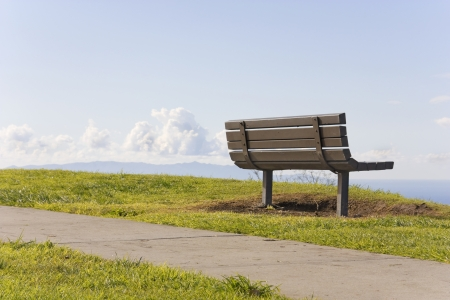 A leisurely stroll    A paved pathway runs along the top of a grassy cliff in a suburban park  A wooden bench top faces a blue sky and clouds, offering a relaxing place to rest after a long walk  photo