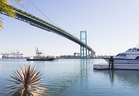 A perspective view under the curved suspension bridge spanning the Port of Los Angeles on a sunny day  Barge passing underneath the suspension bridge with a tugboat at its side  Shipping containers and cranes in the background  A motorboat is docked in th photo