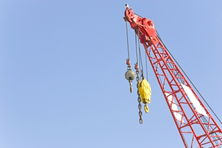 Bright yellow crane hook and grey wreaking ball suspended by cables from a red color crane  View from under the crane  Horizontal with lots of room for text   Stock Photo - 17504341