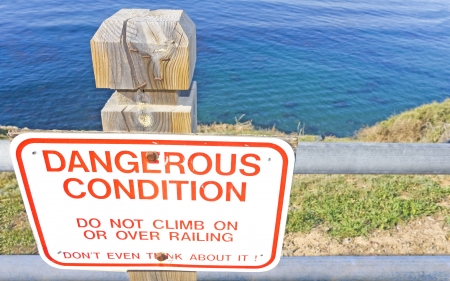 steep cliff sign: Dangerous condition  Bold red letters on a white hazard sign atop a grassy ocean cliff warns against climbing over the metal railing to prevent falling and serious injury  Metal warning sign is attached to a wood fence post  Blue ocean in the background