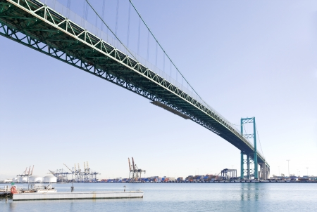 curving: Perspective view under the curving suspension bridge spanning the Port of Los Angeles on a sunny day  Shipping containers and cranes in the background  Focus is on the bridge structure overhead  A small boat dock is in the foreground   Stock Photo