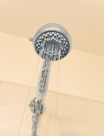 Conserve water concept depicted by a leaking shower head sprayer  Can also be used for a clean, personal hygiene concept  View is from under the shower head  photo