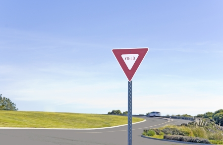 Red and white yield sign in front of a divided rural road  Grass and bushes line the roadway  One car and blue sky in the background  Background is slightly blurred  Stock Photo - 17504338