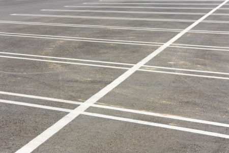 Horizontal view of two rows of vacant parking lot spaces  A single, diagonal thick white dividing line separates the rows    photo