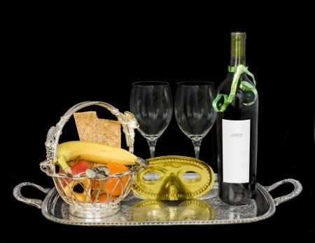 A custom for the Jewish holiday of Purim is to send gift baskets of food and drink to friends, called Mishloach Manot, or Shalach Manot  Shown is a basket with fresh fruit, crackers, hamantashen, wine, glasses and costume mask Stock Photo - 17504324