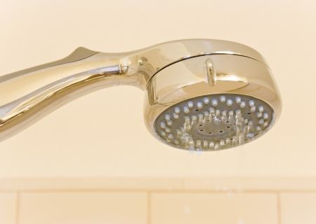 shower stall: Conservation of water concept depicted by water droplets dripping from a shower head  Can also be used for a clean, personal hygiene concept  Close up view of the shiny handle and sprayer