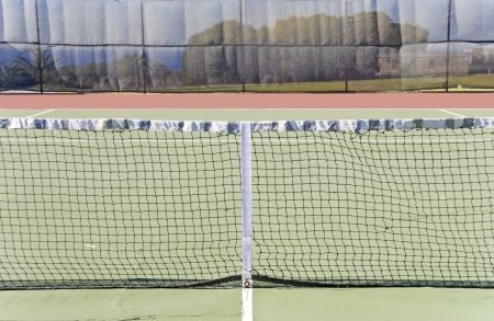 Tennis court with closeup of the net  Tennis court enclosed by a fence  Trees in the background  Stock Photo - 17504349