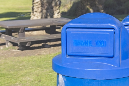 uncluttered: Blue plastic trash can in a clean, suburban park  The words, thank you, appear on the lid  Wood picnic table, large palm tree trunk and grass in the background  Focus is on the trash can
