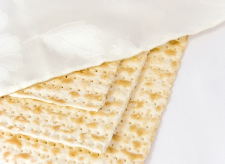 matzo: 3 covered Passover matzahs   Three square matzahs under a decorative white cloth cover for the pesach seder overlapping each other, isolated on a white background   Stock Photo