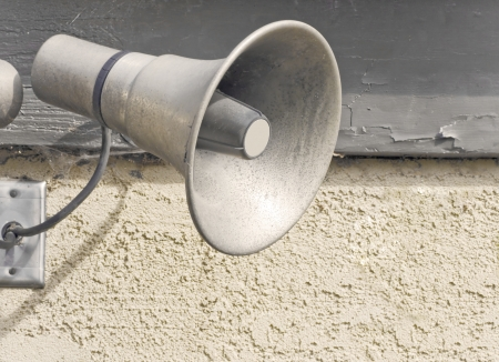 public address: Old, weathered PA system loudspeaker   Public address system bullhorn wired to an outlet on a textured stucco and wood wall  The wood on the wall is chipped and peeling  Stock Photo