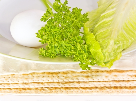 Passover seder plate and matza   Close up of three covered matzas under a ceramic seder plate with hard boiled egg, parsley, and romaine lettuce leaf   photo
