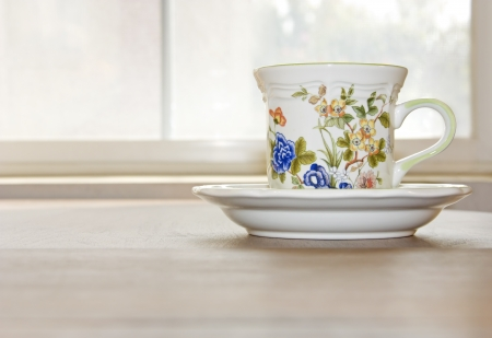 Morning tea by the window   Elegant cup and saucer on a wood table  Window with bright morning light shining in the background  Horizontal scene, room for text   photo