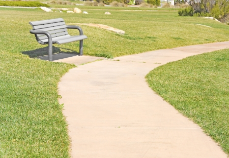 Comfy bench   A park bench sits beside a peaceful, empty, winding pathway curving through a green grassy field in a suburban park  Horizontal view  Bright sunny day  photo