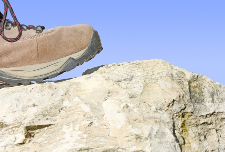 On a hike with rock and sky   Front profile of a suede leather, black and brown hiking shoe stepping on a rock with blue sly in the background   The toe of the shoe is raised slightly  Horizontal view   Stock Photo - 18120760
