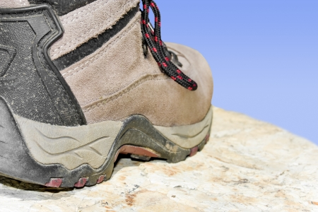 sturdy: Hiking boot, rock, and sky   Closeup, low angle view of one sturdy, black and brown hiking shoe on a rock with blue sly in the background  Horizontal, rear view  Selective focus on the heel of the shoe  Stock Photo