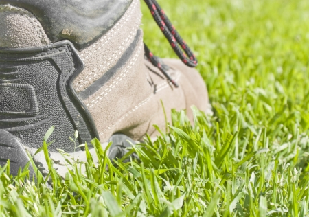 sturdy: One step at a time   Closeup, low angle view of one sturdy, black and brown hiking boot stepping in the grass  Horizontal, rear view  Selective focus on the heel of the shoe
