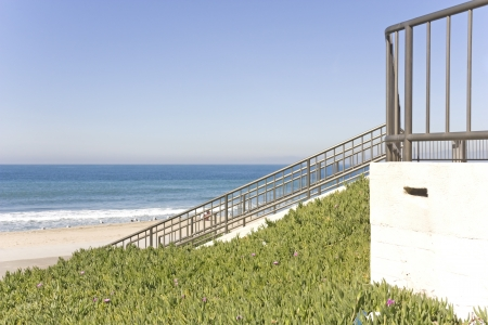 groundcover: To beach bike path and sand   Beach access via a concrete structure with fence, ramp and metal railing going down to the sand  Blooming, green succulent ice plant with small purple flowers serves as groundcover at the slope adjacent to the building