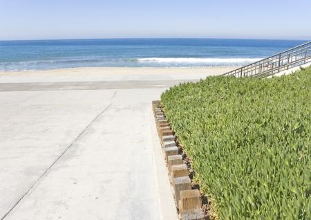 going down: Acceso a la playa a trav�s de un pasillo ancho, pavimentado peatonal bajar al carril bici y la arena debajo de la planta verde hielo suculenta delimitado por postes de madera sirve como cubierta vegetal para la rampa de pendiente del terreno y la barandilla de metal tambi�n bajar a la arena en el backgrou
