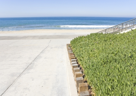 Beach access via a wide, paved pedestrian walkway going down to the bike path and sand below  Green succulent ice plant bounded by wood posts serves as groundcover for the sloping terrain  Ramp and metal railing also going down to the sand in the backgrou Stock Photo - 18120794