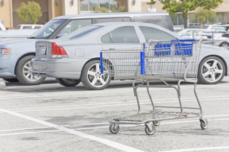 Empty shopping cart   Abandoned, empty metal grocery cart in a suburban parking lot  Cars, store buildings in the background  Horizontal view  Stock Photo - 18600248