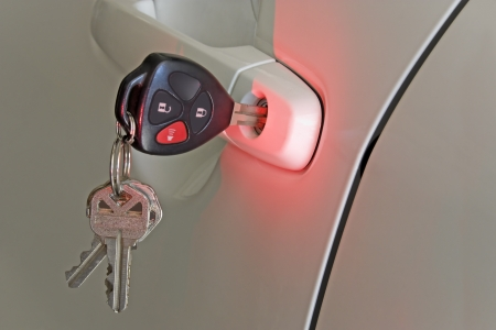 key fob: Nighttime car door safety   A red light shines on a car door lock to make the keyhole easy to find at night  Car key is inserted in the lock  Other keys hang from the key ring  The wireless remote is part of the key fob