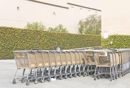 Outdoor rows of shopping carts   Perspective view of metal and plastic grocery carts attached to one another in long rows beside a suburban shopping mall building wall  photo