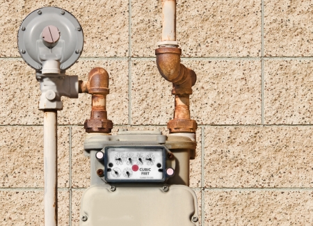 gas meter: Residential natural gas meter   Home gas meter and rusty piping against a brick wall textured background  Horizontal view  Stock Photo