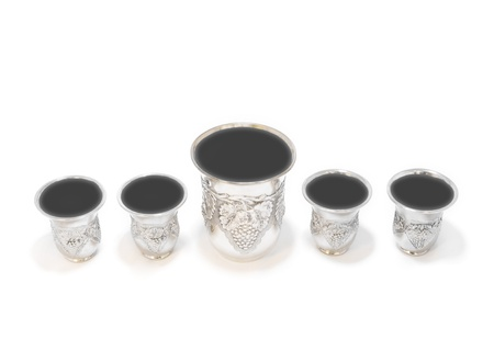 kiddush: Cups of wine for the Pesach seder   Five shiny, decorative silver cups filled to the brim with red wine  The large wine cup, called Elijah