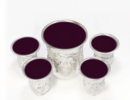 brim: Cups of wine for the Passover seder   Five shiny, decorative silver cups filled to the brim with red wine  The large wine cup, called Elijah
