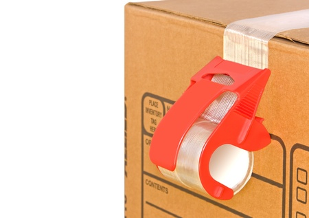 Cardboard box and adhesive tape roll dispenser   Close up, red tape dispenser sealing a brown corrugated box  Strong, sticky tape suitable for mailing packages  Isolated on a white background  Room for text  photo