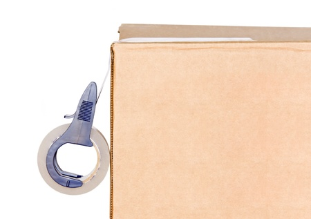Corrugated box and adhesive tape roll dispenser   Close up, blue tape dispenser sealing a brown corrugated box  Strong, sticky plastic tape suitable for mailing packages  Isolated on a white background  Room for text  photo