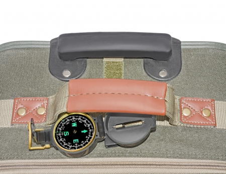 Travel bag and compass   Top, close up view of khaki color cloth suitcase with leather grip and plastic retractable handle  Open compass with dial showing degrees and bearings rests on top of the bag  photo