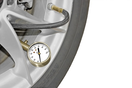 sidewall: Measuring tire pressure   Car tire pressure gauge, tire wheel and sidewall close up  Room for text  Meter rests inside tire wheel, attached to the stem  Copyspace, isolated on a white background