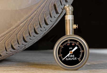 sidewall: Car tire pressure gauge, tire tread and sidewall close up   Pressure meter stands upright against tire profile on a grey concrete floor  Black background