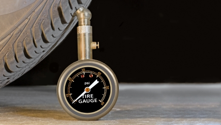 sidewall: Car tire pressure gauge, tire tread and sidewall close up  Room for text   Pressure meter stands upright against tire profile on a grey concrete floor  Black background  Lots of copyspace