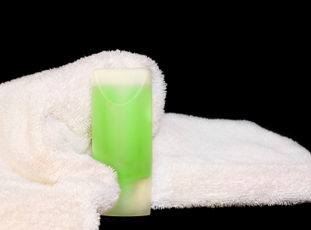 towel wrapped: Comfy bath towel and bottle   Soft, fluffy white towel wrapped around a plastic bottle filled with green shampoo, body wash, lotion, or gel  Nice for a luxurious relaxation or wellbeing concept  Isolated on a black background