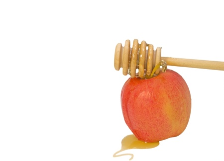 Honey stick and apple for Rosh Hashana Symbols of the Jewish New Year  Sweet golden honey flowing over a wood stick on to a fresh red apple  Puddle of honey in the foreground  Isolated on a white background  Copyspace  Horizontal photo  Stock Photo - 20260071